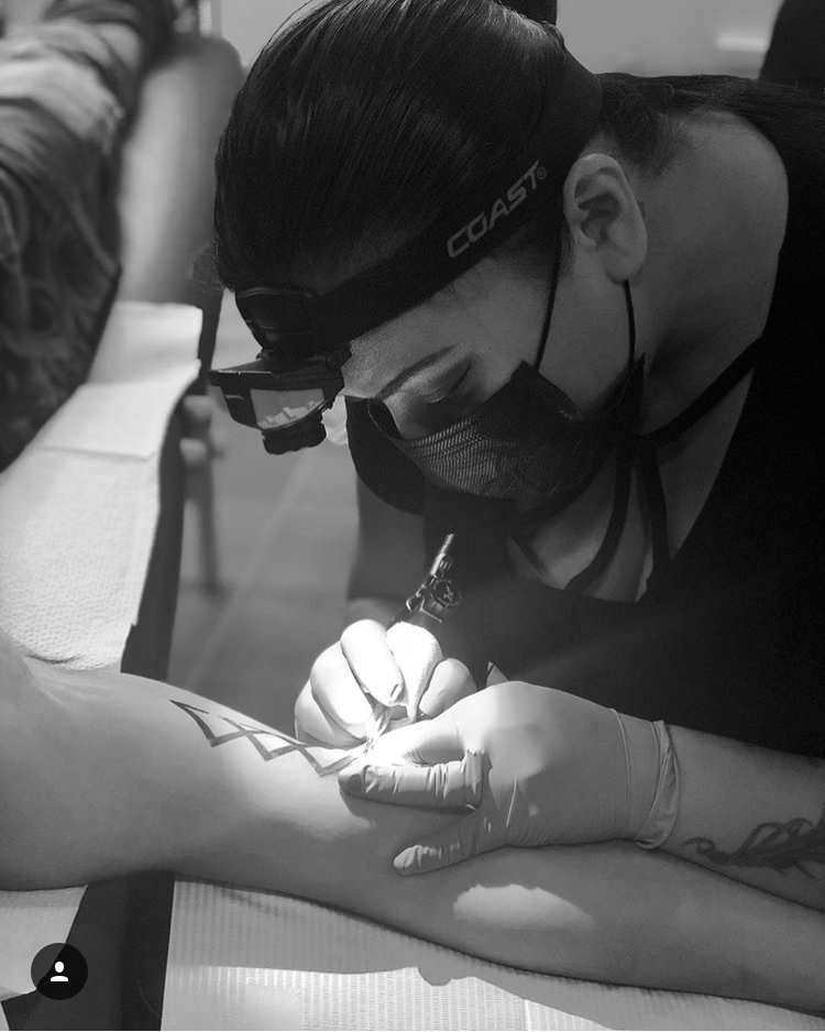 woman tattoo artist tattooing a arm